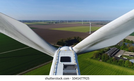 Aerial close up photo of wind turbine in polder landscape showing the white modern construction of the wind turbine device that converts winds kinetic energy into electrical energy
