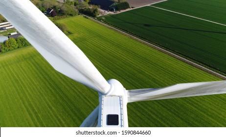 Photo de gros plan aérienne d'une éolienne fournissant de l'énergie durable par des pales de rotation l'énergie aussi connue sous le nom d'renouvelable est collectée à partir de ressources prairie verte en arrière-plan
