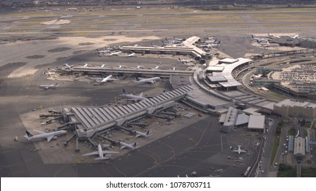 AERIAL, CLOSE UP: Flying above airplanes parked on apron waiting for passengers to board through jetway and start their traveling journey. Terminal building on New York Newark international airport