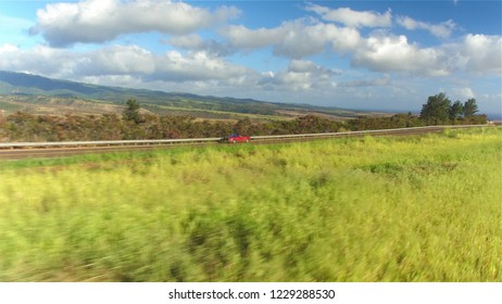 AERIAL CLOSE UP: Luxury red convertible car driving on countryside road along the stunning Waimea canyon in lush Hawaii island. Happy man and woman traveling on sunny summer vacation