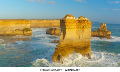 AERIAL CLOSE UP: Ocean waves splashing into famous Twelve Apostles formation along the rocky Australian shore at Great Ocean Road. Flying past famous Twelve Apostles in sunny summer evening