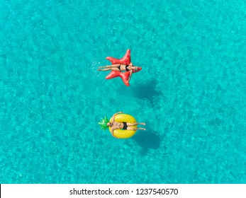 Aerial close up view of couple floating on inflatable star and pineapple shaped mattresses holding hands.