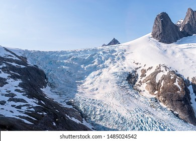 aerial closeup of a mountainside portion of gilkey glacier in alaska from a helicopter with clear blue sky in the background