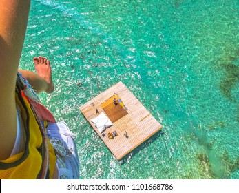 Aerial closeup view of a woman parasailing. Below, the landing platform on the spectacular blue sea of Deer Island, east coast of Mauritius, Indian Ocean.