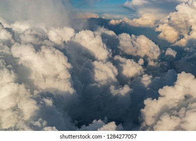 Aerial cloudscape with big fluffy clouds illuminated by sun