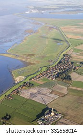 Aerial coastal view of the shore of Ameland Frisian Island with green fields, dike and sea, The Netherlands