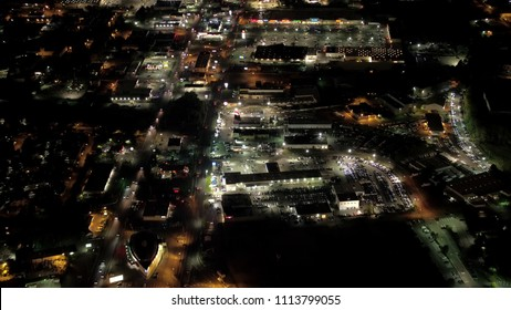 AERIAL: Commercial shopping centers and parking lots lit up with lights at night