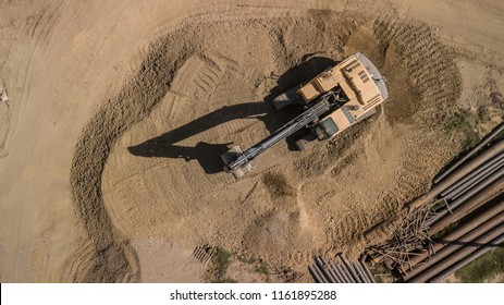 Aerial construction site with machinery, bulldozer, excavation. Top down view of city building site.