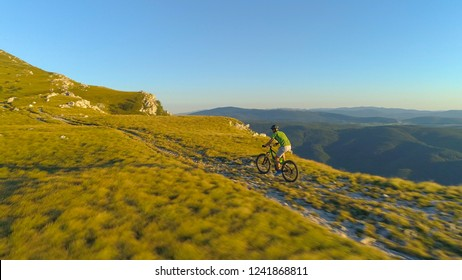 AERIAL: Cool shot from above of extreme cyclist speeding down a scenic grassy hill in the sunny backcountry. Picturesque green nature surrounding male downhill rider pedalling down the grassy trail.