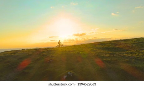 AERIAL, COPY SPACE, LENS FLARE, SILHOUETTE: Flying along a fit male tourist on a fun mountain biking adventure as he climbs a steep grassy hill on a sunny spring evening. Tourist riding an ebike.