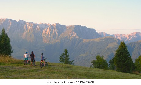 AERIAL COPY SPACE: Three friends on mountain bikes observe scenic sunlit mountains on a beautiful summer day. Tourists on ebikes look around the summer evening nature after fun journey across Slovenia