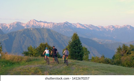 AERIAL, COPY SPACE: Young tourists on ebikes look around the scenic summer evening nature after a fun mountain biking trip in Slovenia. Fit friends plan their route for a mountain biking adventure.