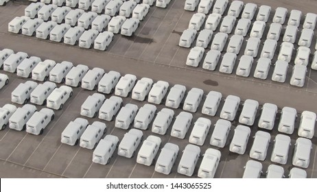 AERIAL Countless cars wrapped in white paper are parked in a massive storage park by a busy harbor. Brand new cars waiting to get exported to their destination country. Large car dealership stock.