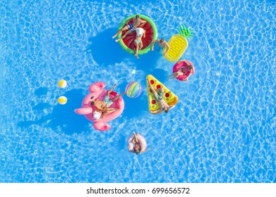 AERIAL: Couples and friends hanging out on fun floaties in luxury resort pool