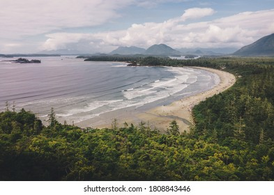 Aerial of Cox Bay beach Tofino with ocean waves and mountains in background