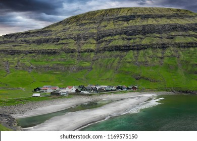 AERIAL: Dark clouds gather over the serene oceanfront village in the picturesque green valley. Stunning background of a tranquil town protected by steep hill in the scenic countryside of Faroe Islands