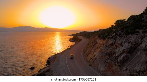 AERIAL: Dark colored car cruises along the scenic coastal road illuminated by the picturesque orange sunset. Tourists on fun summer road trip in Lefkada exploring the picturesque island at sunrise.