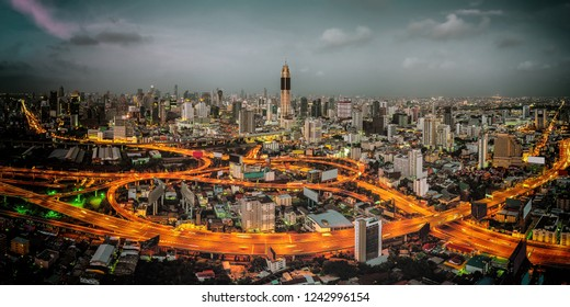 An aerial dawn shot of a glowing highway in downtown Bangkok.