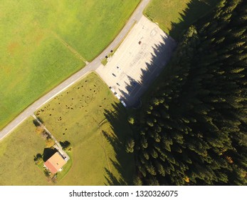 Aerial daylight drone down view swiss Jura landscape with road, cows and parking place close to La Brevine, CH Switzerland. 05th Oct. 2018