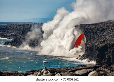 Aerial daytime view of top portion of waterfall shaped flow of red lava from volcano in Hawaii and the beach below