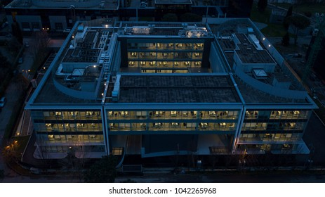 Aerial detail of the windows of an office where people still work despite being outside night. The darkness hides what is outside the building, used as an office.