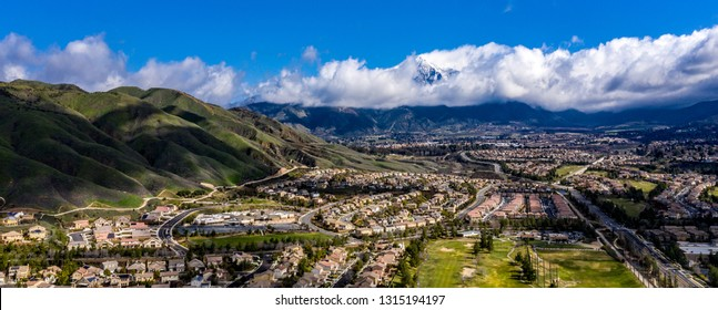 Aerial, done view of white clouds over Mount San Gorgonio in the San Bernardino Mountains and blue sky above Yucaipa, California after a rain storm