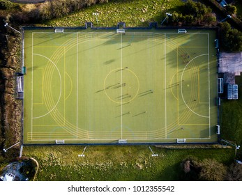 An aerial downward view of people playing football on a pitch in Kinsbridge, Devon, UK