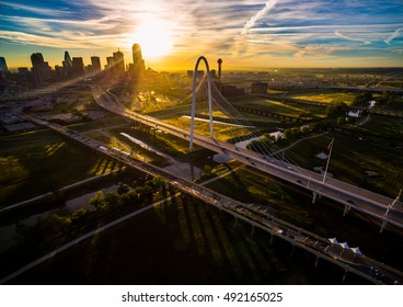 Aerial Dramatic Sunrise Starburst with shadows and amazing Cityscape into the Sun with the Margaret Hunt Hill Bridge over Trinity Overlook Park aerial drone shot above Dallas Texas