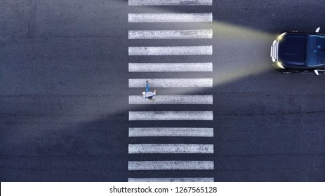 Aerial. Driving in low light conditions. Pedestrian crossing and one car with headlight. Night transportation top view.