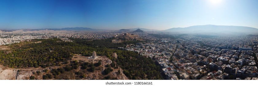 Aerial drone bird's eye panoramic view of iconic monument of Filopapou and Acropolis hill with famous temple of Parthenon at the background, Athens historic centre, Attica, Greece