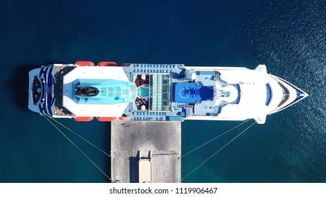 Aerial drone bird's eye top view photo of large cruiser ship docked in deep blue water mediterranean port