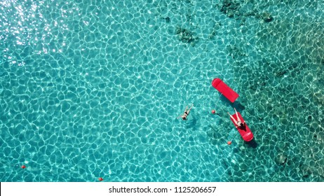 Aerial drone bird's eye top view of couple sitting in inflatable pools and matress in rocky emerlad water tropical caribbean resort