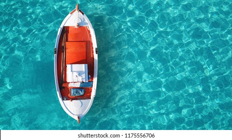 Aerial drone bird's eye top view of colourful traditional fishing boat in turquoise clear waters of Super Paradise beach, Mykonos island, Cyclades, Greece