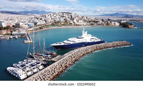 Aerial drone bird's eye view photo of iconic beach near port of Marina Zeas with boats docked with beautiful scattered clouds, port of Piraias , Attica, Greece