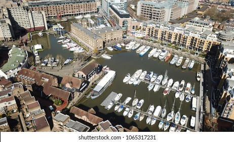 Aerial drone bird's eye view of famous St Katharine Docks Marina and iconic skyline in City of London, United Kingdom