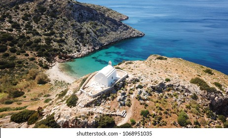 Aerial drone bird's eye view of famous beach of Galissas with small picturesque church of Agios Pakos, Syros island, Cyclades, Greece