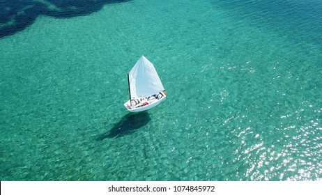 Aerial drone bird's eye view photo of small sail boat cruising in turquoise clear waters