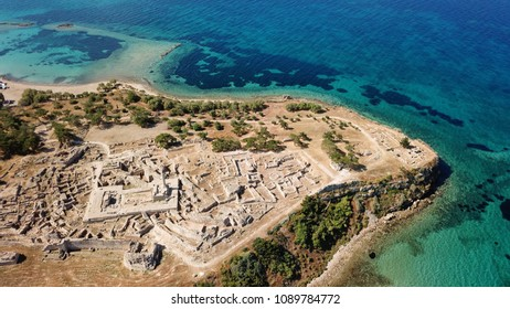 Aerial drone bird's eye view of iconic temple of Apollo on top of Kolona hill with only one pillar left standing, Aigina island, Saronic gulf, Greece