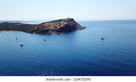 Aerial drone bird's eye view of luxury yachts docked in bay below archaeological site of Cape Sounio, Temple of Poseidon, Attica, Greece