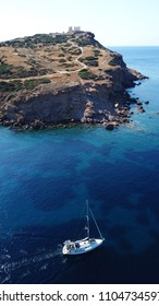 Aerial drone bird's eye view of luxury yacht cruising in bay below iconic archaeological site of Cape Sounio, Temple of Poseidon, Attica, Greece