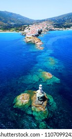 Aerial drone bird's eye view of iconic lighthouse of Tourlitis built at sea in port of Andros island chora, Cyclades, Greece