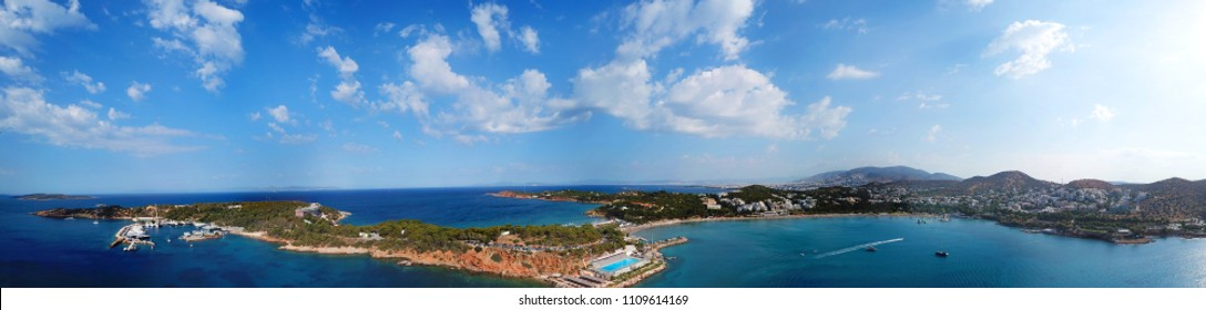 Aerial drone bird's eye view panoramic ultra wide 180 degrees photo of iconic Astir beach and Peninsula with beautiful scattered clouds, Vouliagmeni, Athens riviera, Attica, Greece