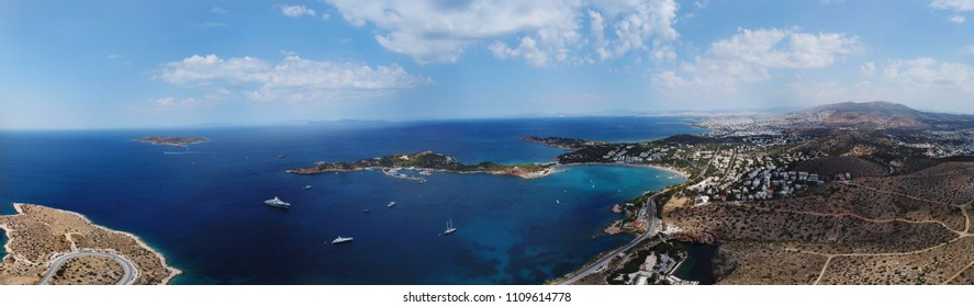 Aerial drone bird's eye view panoramic ultra wide 180 degrees photo of iconic Astir beach and Peninsula and lake Vouliagmeni, Athens riviera, Attica, Greece