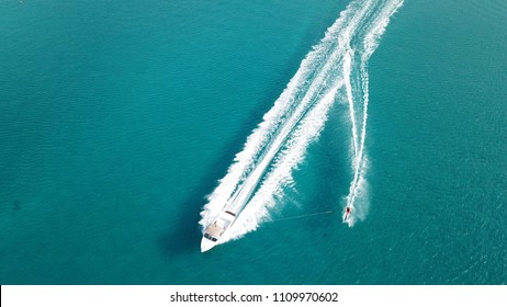 Aerial drone bird's eye view photo of man practicing water ski in tropical beach