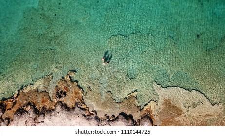 Aerial drone bird's eye view photo of people swimming in emerald clear waters of tropical paradise