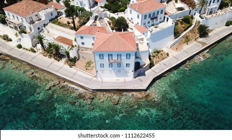 Aerial drone bird's eye view photo of picturesque neoclassic houses built in emerald water waterfront in historic and traditional island of Spetses, Saronic Gulf, Greece
