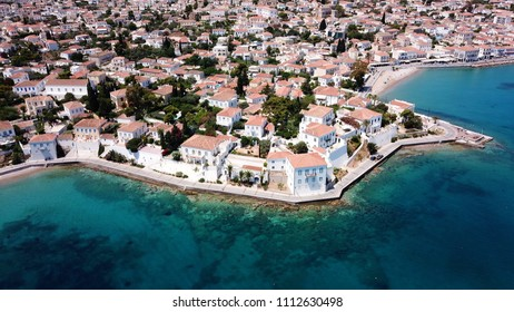 Aerial drone bird's eye view photo of picturesque neoclassic houses in historic and traditional island of Spetses with emerald clear waters, Saronic Gulf, Greece