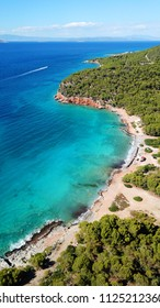 Aerial drone bird's eye view photo of emerlald and sapphire clear water rocky beach found in mediterranean island covered with pine trees