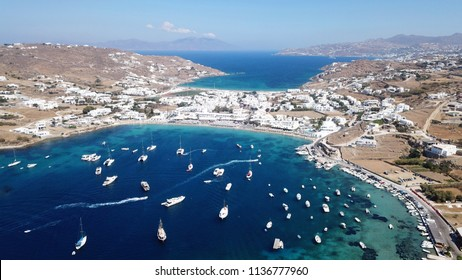 Aerial drone, bird's eye view photo of famous crowded full of sun beds turquoise colour sandy beach of Ornos, Mykonos island, Cyclades, Greece
