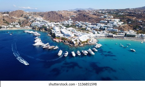 Aerial drone, bird's eye view photo of luxury yachts docked near turquoise sea in paradise beach of Psarou and Platy Gialos full of pool resorts and rocky seascape, Mykonos island, Cyclades, Greece